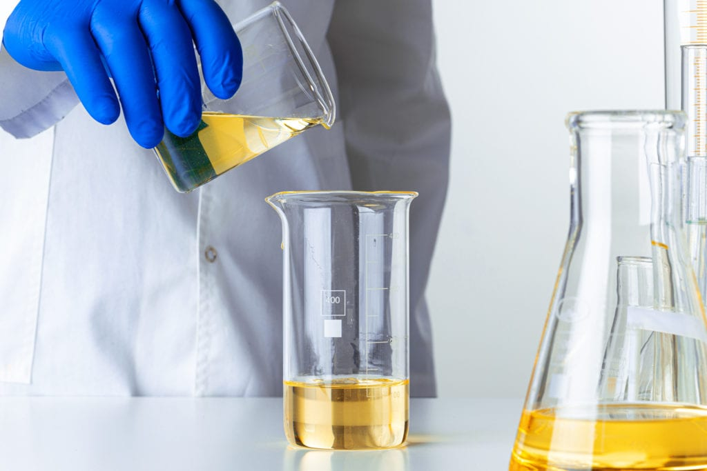 Scientist or doctor in blue gloves pouring some yellow liquid into a flask